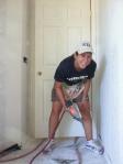 Girl nailing a baseboard